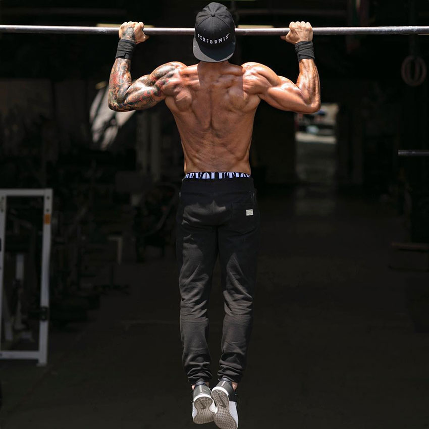 Michael Vazquez performing a pull up showing off his back muscles.
