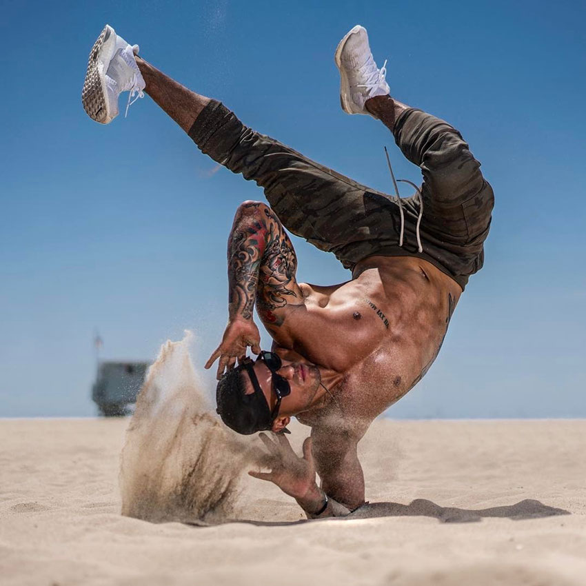Michael Vazquez performing a break dancing move on the beach.