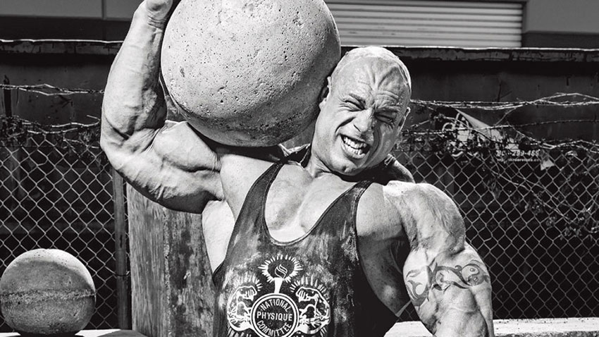 Morgan Aste carrying an atlas stone at a strongman event