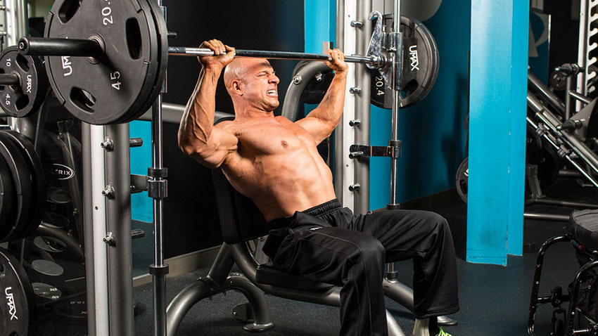 Nick Scott performing an incline chest press on a Smith machine.