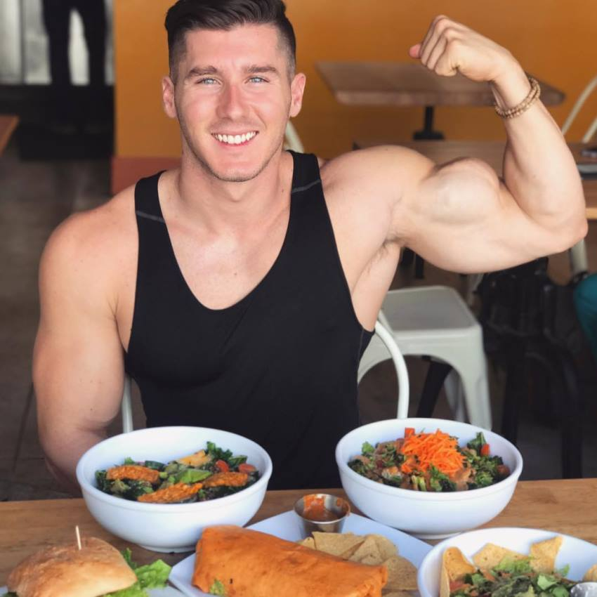 Nimai Delgado sitting with vegan food on the table and flexing his biceps