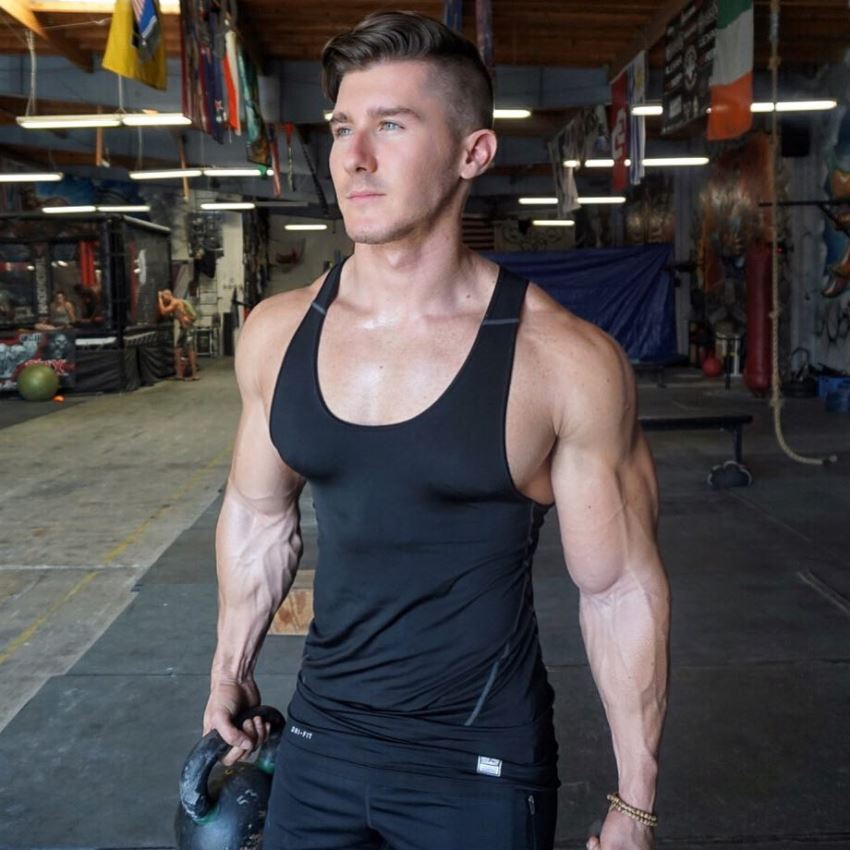 Nimai Delgado standing in the gym posing for a photo in black tank top, looking ripped