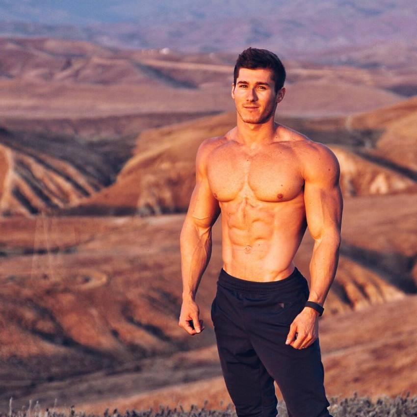 Nimai Delgado standing shirtless on top of a red canyon, looking lean and muscular
