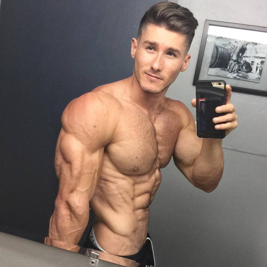 Nimai Delgado taking a selfie of his flexed triceps and obliques in a mirror