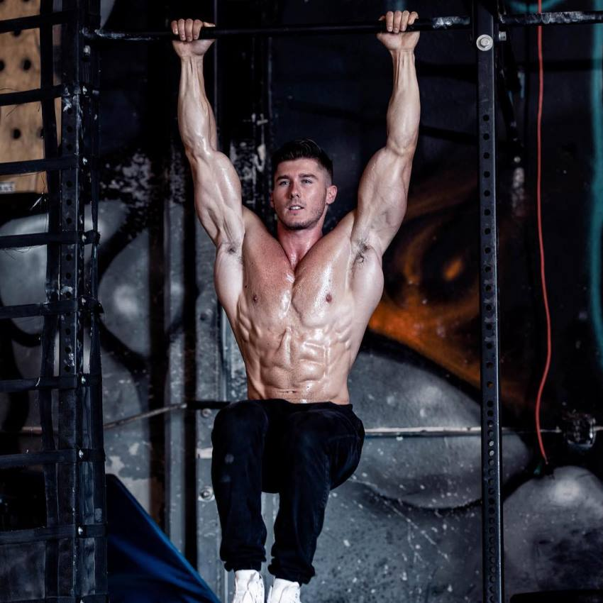 Nimai Delgado doing hanging leg raises shirtless, looking conditioned and muscular