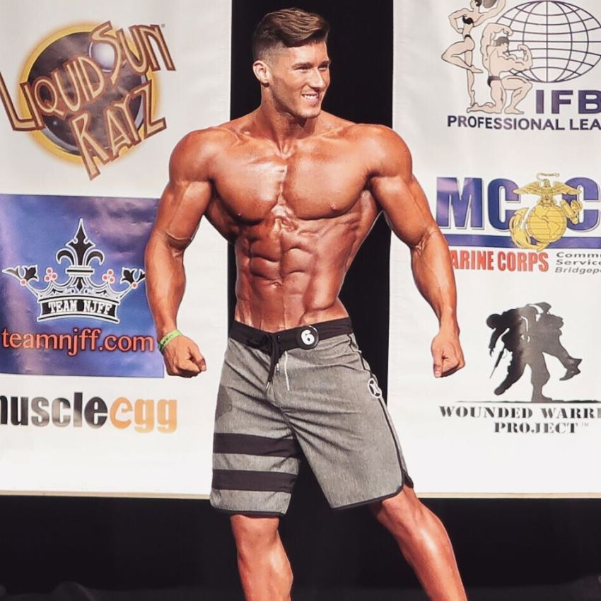 Nimai Delgado on a Men's Physique stage looking ripped and muscular