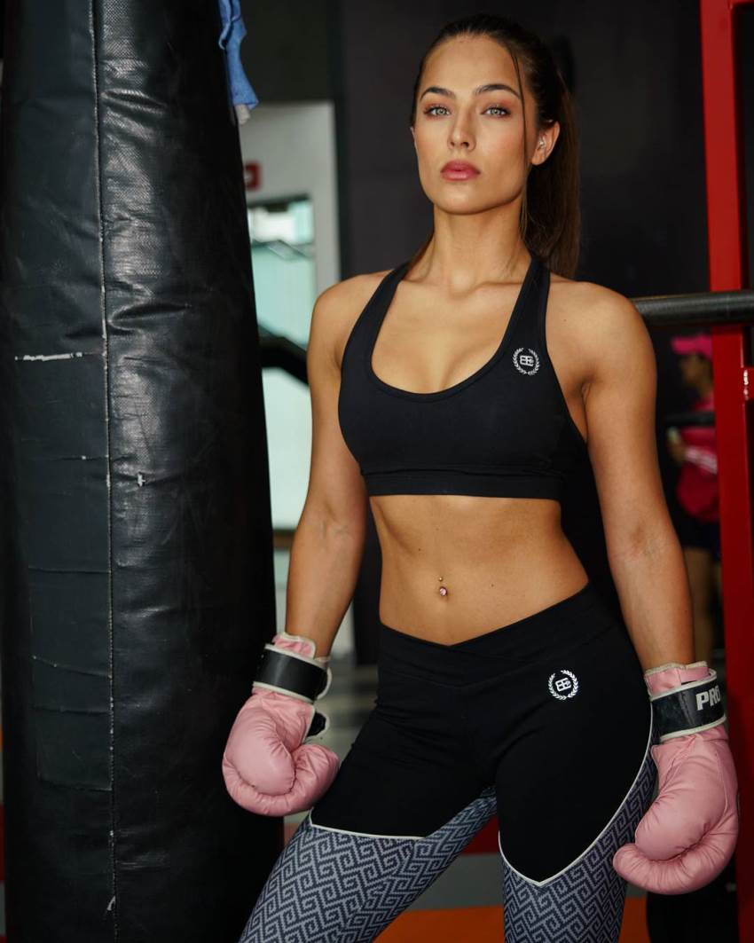 Nochtli Peralta Alvarez by the boxing bag wearing gloves and posing for a photo