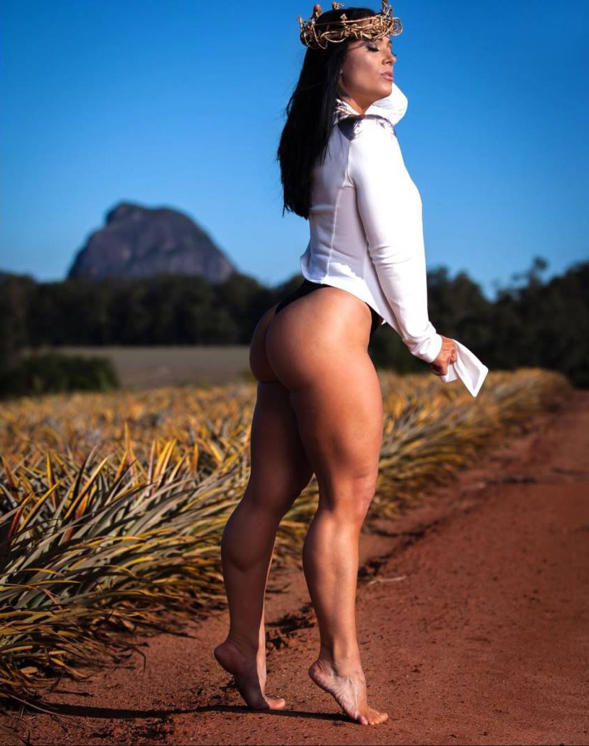 Liz Calles flexing her glutes outside wearing a white top