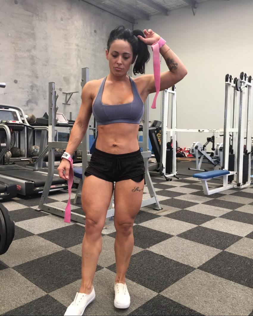 Nyssa Bovenkamp standing in the gym and posing for a photo, looking fit and lean