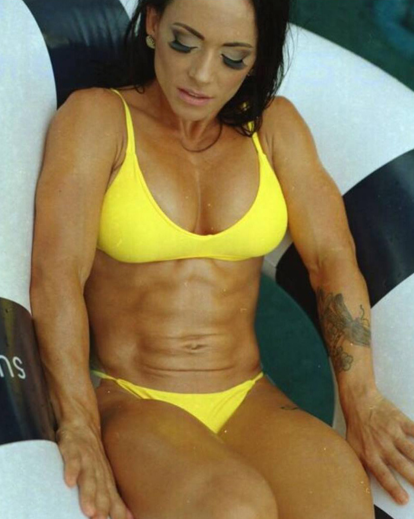Nyssa Bovenkamp flexing her abs whilst sitting down, looking lean and fit