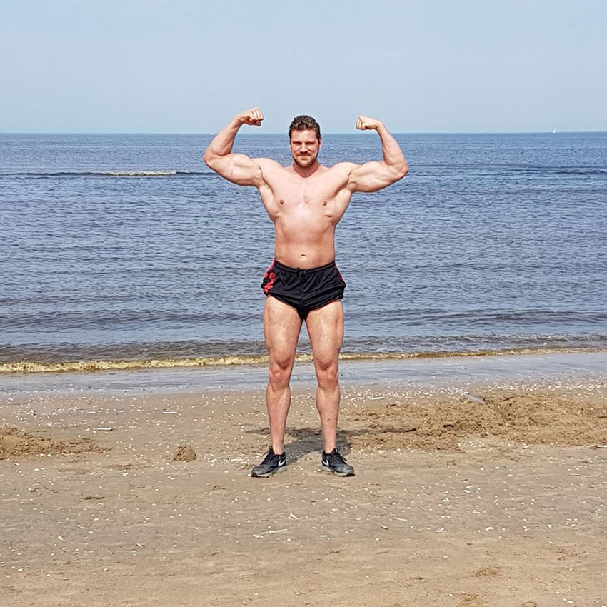 Olivier Richters flexing his biceps on the beach.