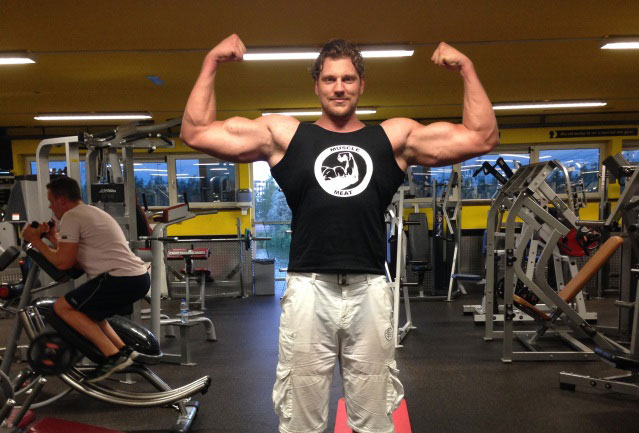 Olivier Richters flexing his biceps in the gym.