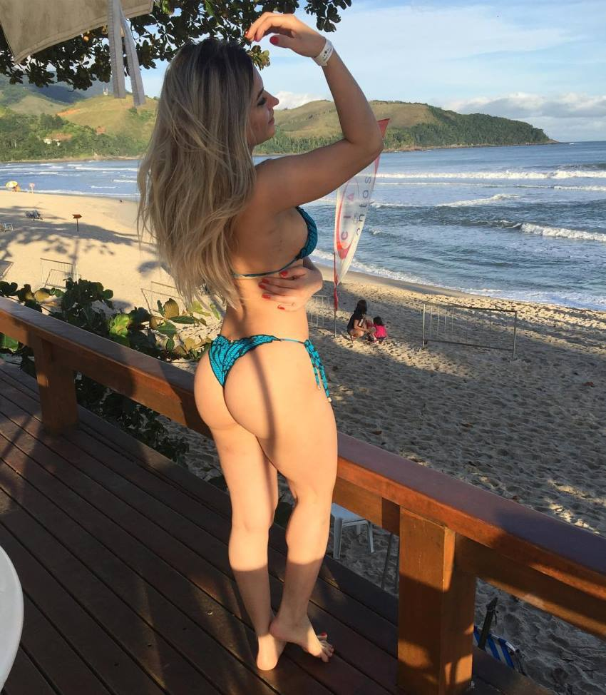 Raissa Barbosa standing on the porch near a beach, looking curvy and fit