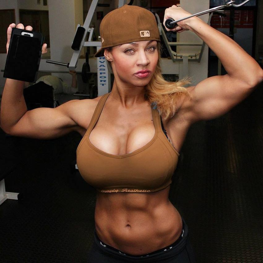 Ramona Valerie Alb flexing her arms and abs while doing one-arm cable biceps curls