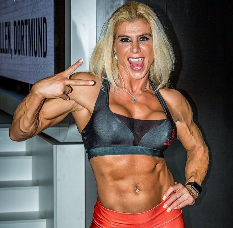 Regiane Da Silva Botthof showing a peace sign to the camera and flexing her ripped abs