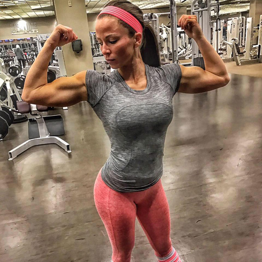 Sarah Bowmar flexing her arms in the gym.