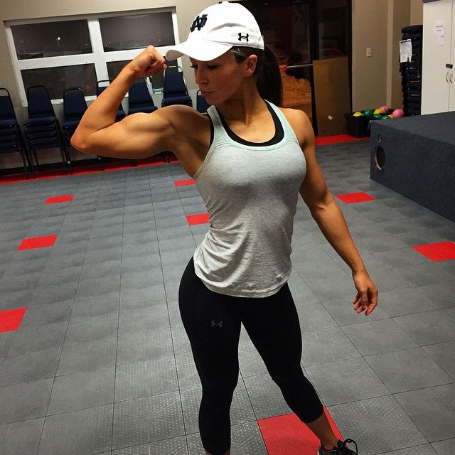 Sarah Bowmar flexing her arm in the gym.