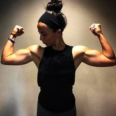 Sarah Bowmar flexing both biceps