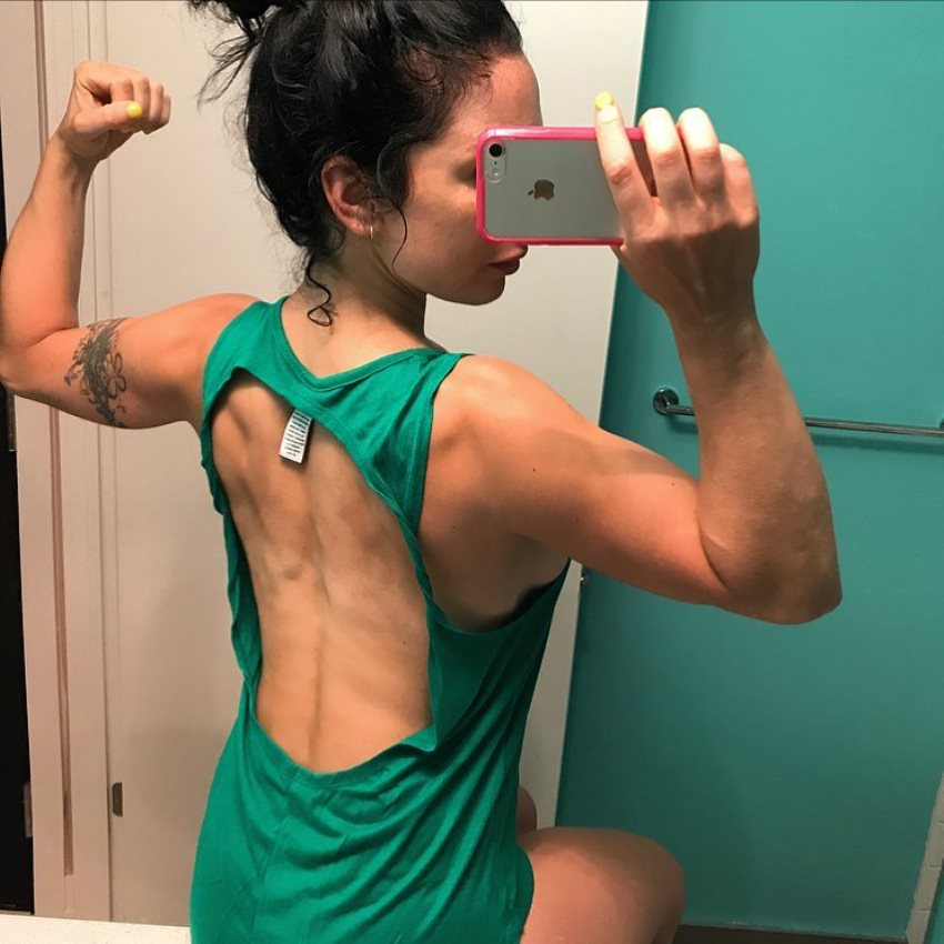 Sarah Van Dusen taking a selfie of her back and arms