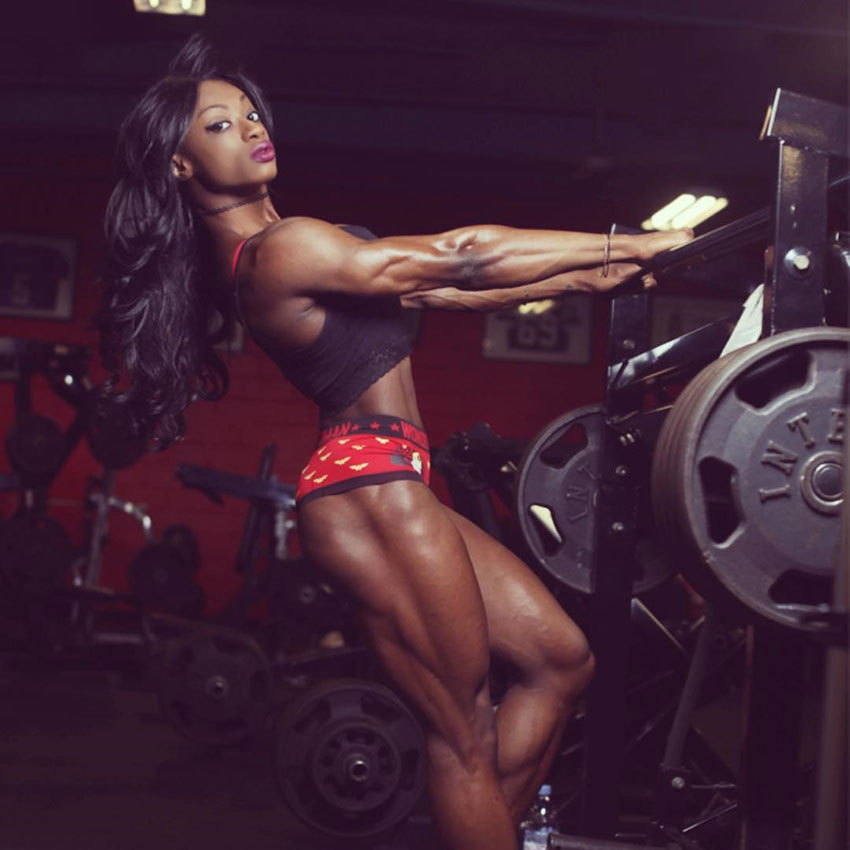 Shanique Grant holding onto a weight rack in a photo shoot.