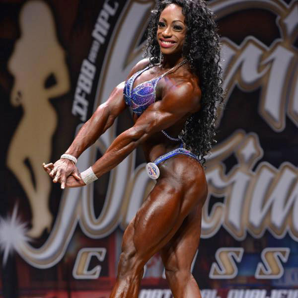 Shanique Grant posing on stage at a bodybuilding show.