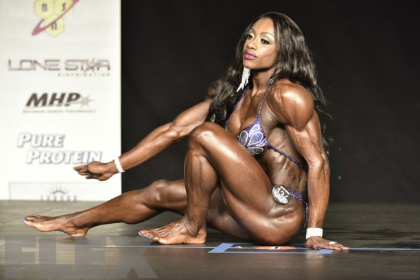 Shanique Grant sat on the floor on stage at a bodybuilding competition.