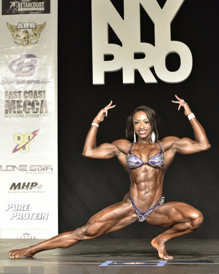 Shanique Grant at a bodybuilding show in New York holding a pose.