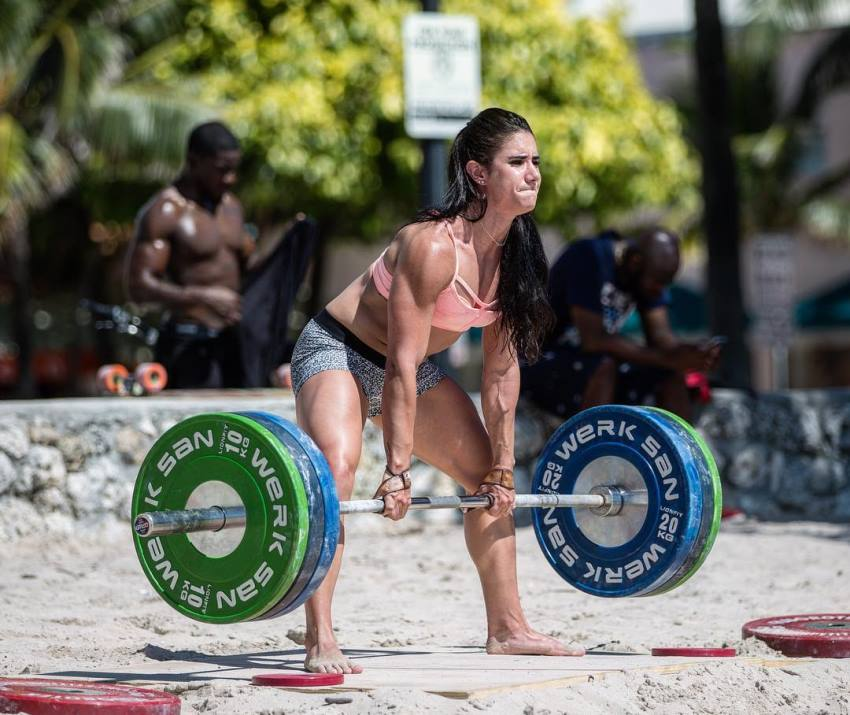 Stefanie Cohen doing heavy deadlifts on sand, looking strong and muscular