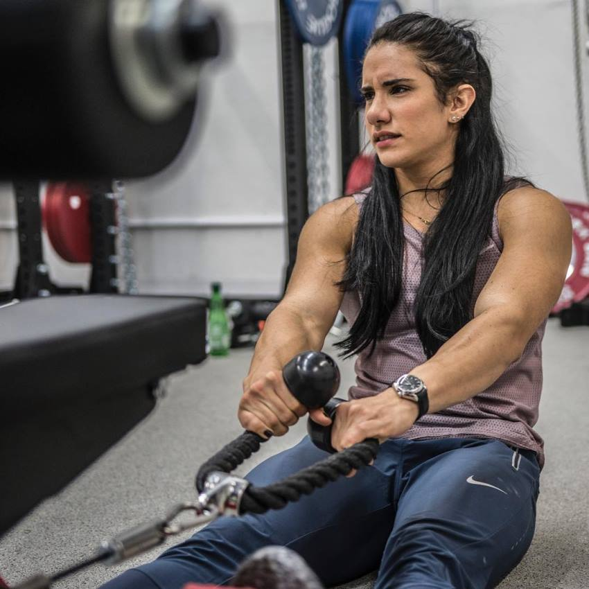 Stefanie Cohen doing cable rows with a tired expression on her face