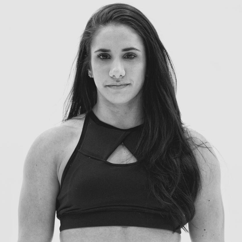 Stefanie Cohen looking at the camera wearing sportsbra