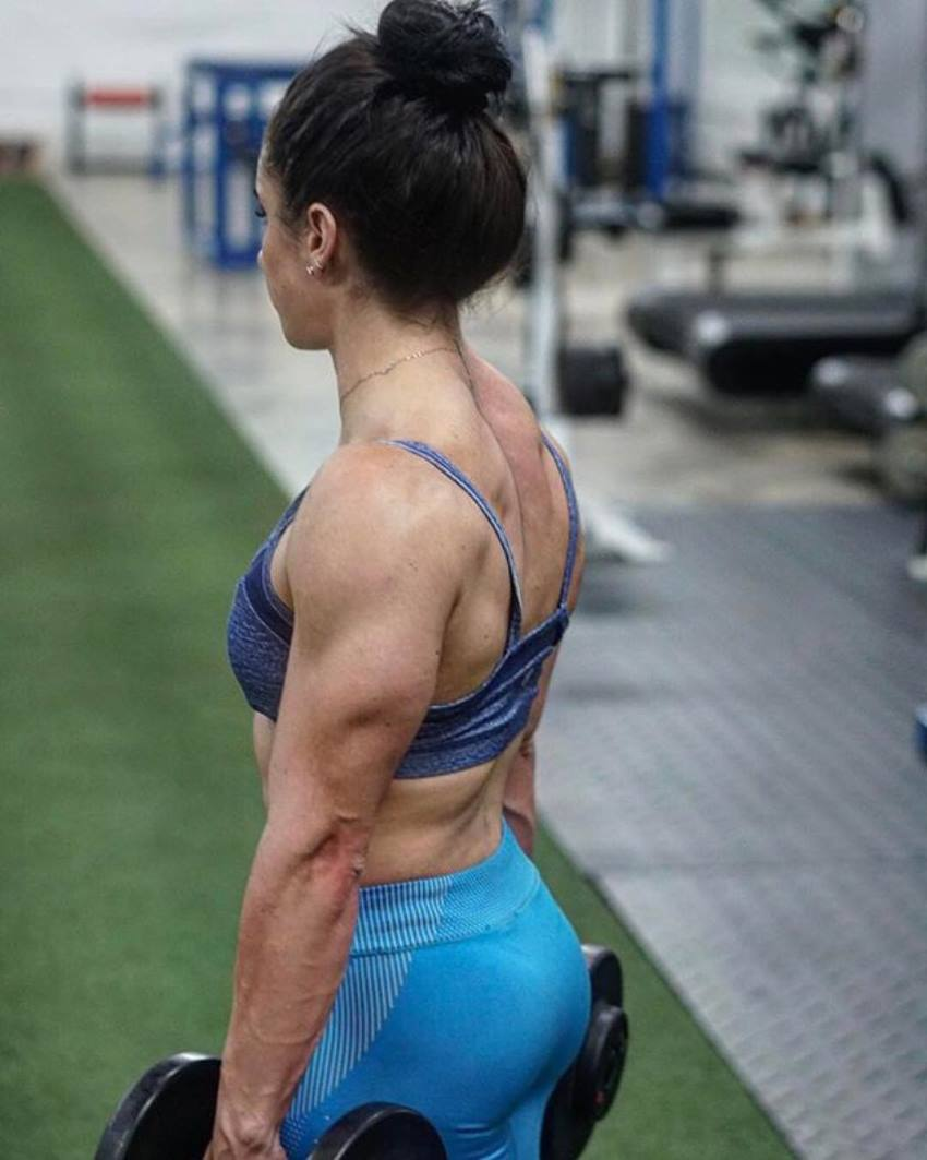 Stefanie Cohen holding dumbbells and showing her muscular triceps and back