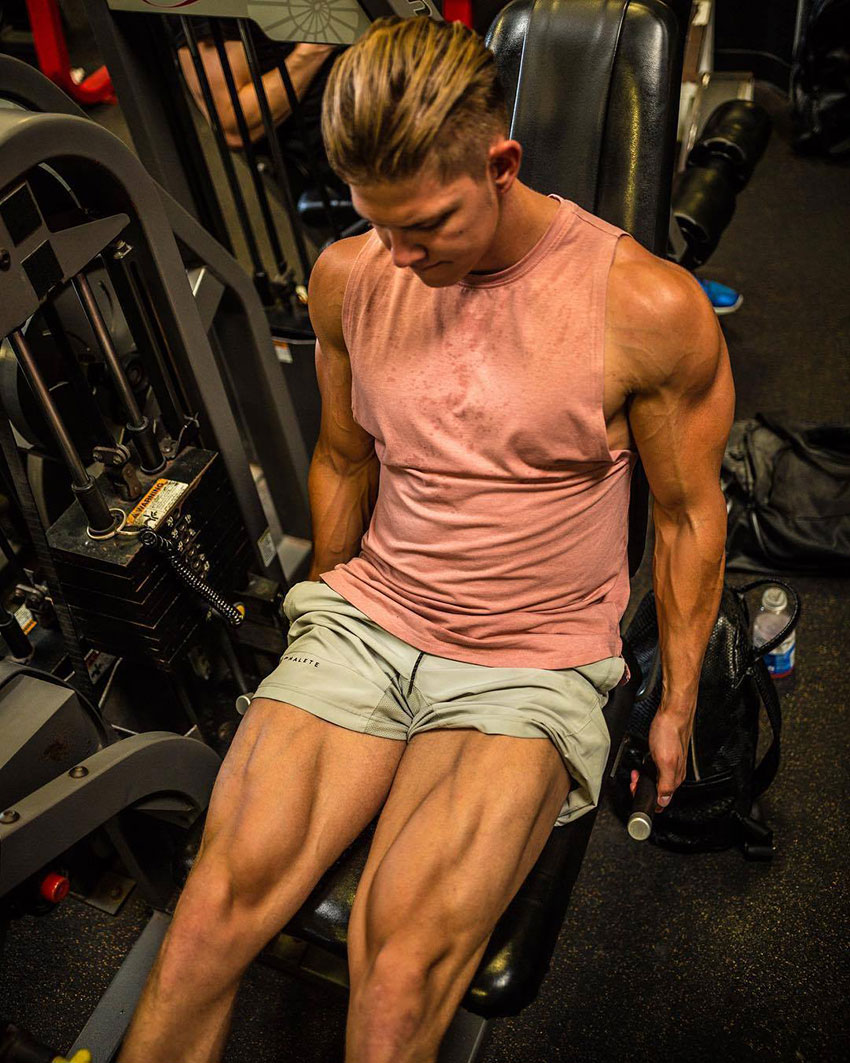 Student Aesthetics performing leg extensions in the gym.