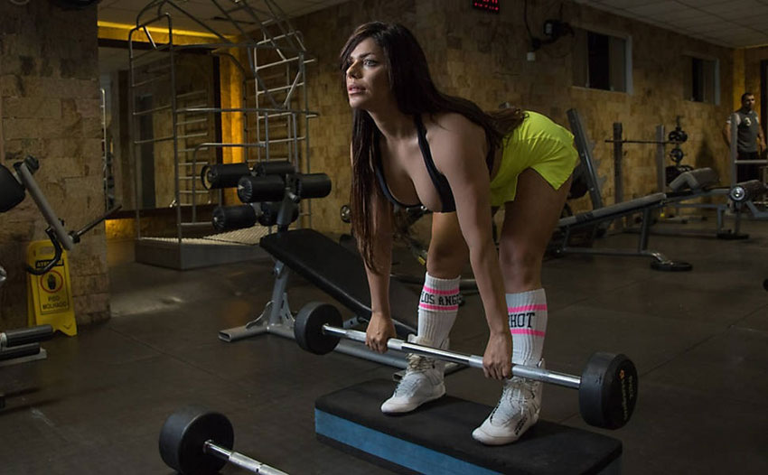 Suzy Cortez performing barbell rows in the gym.