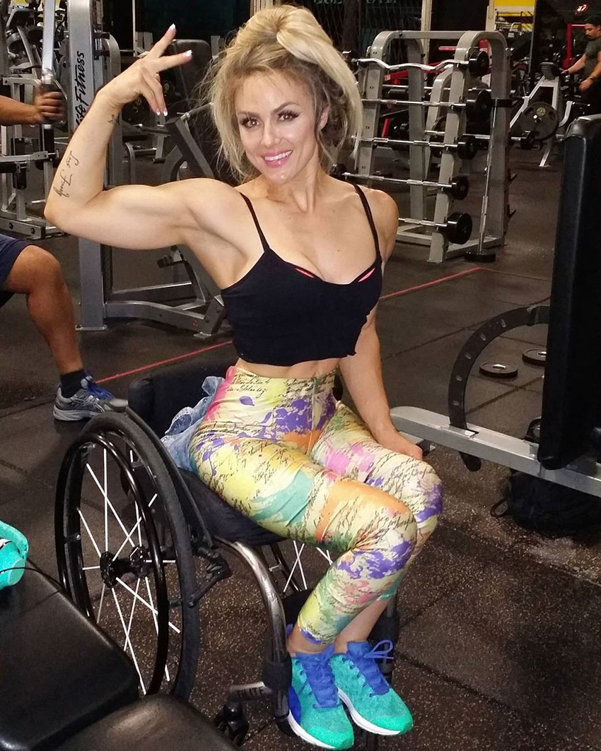 Tiphany Adams flexing her bicep in the gym.