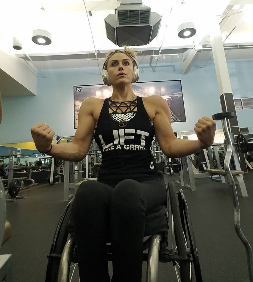 Tiphany Adams tensing her arms in the gym.