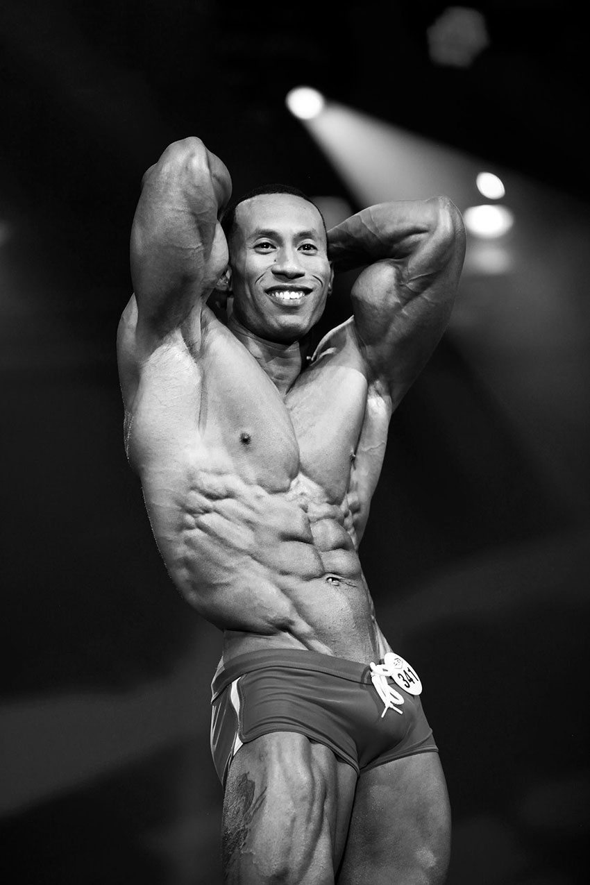 AJ Ellison showing his abs on stage.