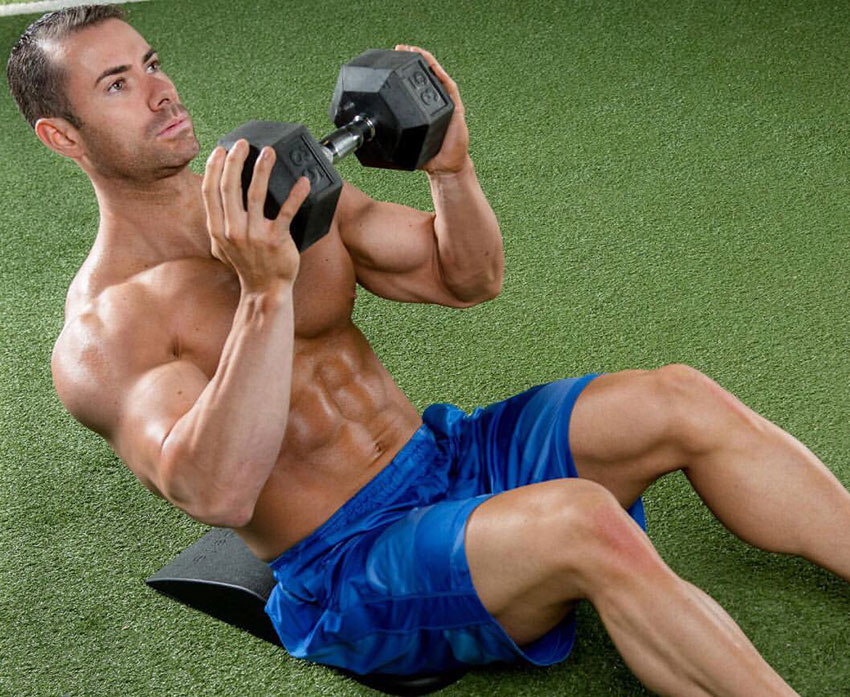 Alex Carneiro exercising in the gym with a dumbbell.
