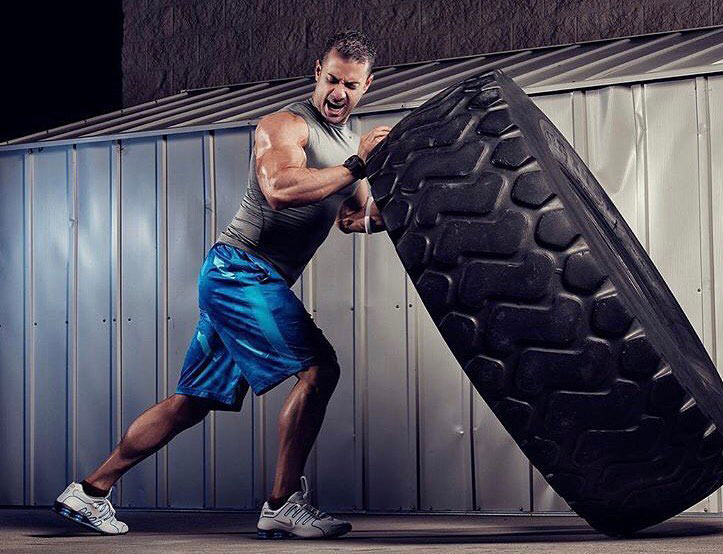 Alex Carneiro exercising in the gym with a tire.