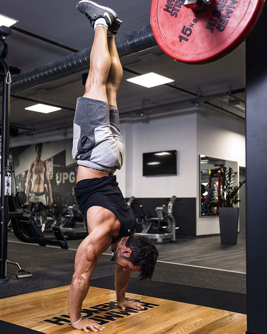 Alon Gabbay performing a handstand in the gym.