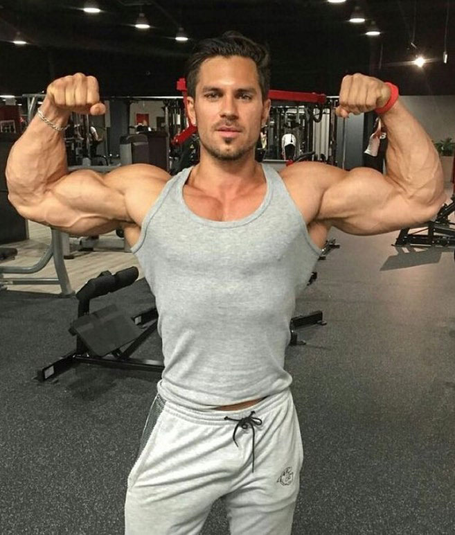 Alon Gabbay flexing his biceps in the gym.