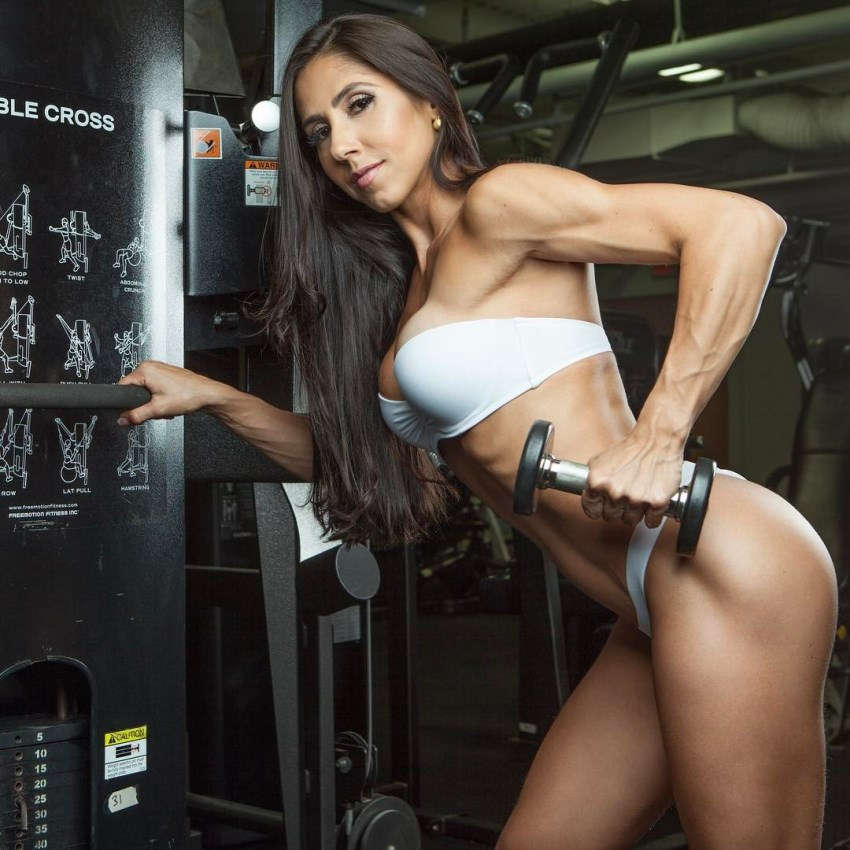 Angelica Teixeira lifting a dumbbell up with her ripped and vascular arm
