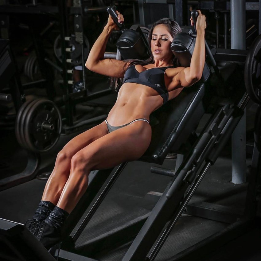 Angelica Teixeira doing hack squats in the gym looking lean and fit
