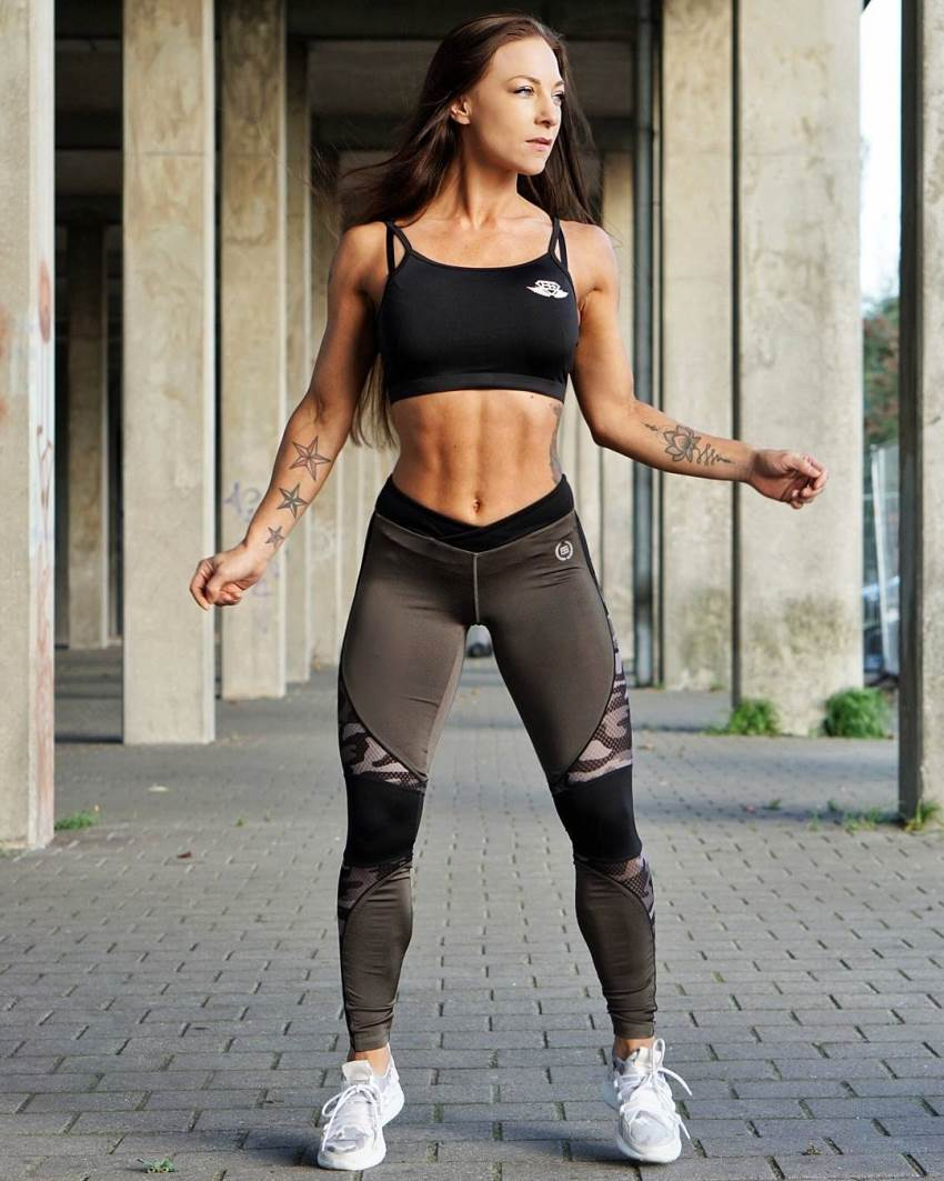 Anna Delyla standing in gym leggings and sports bra looking fit