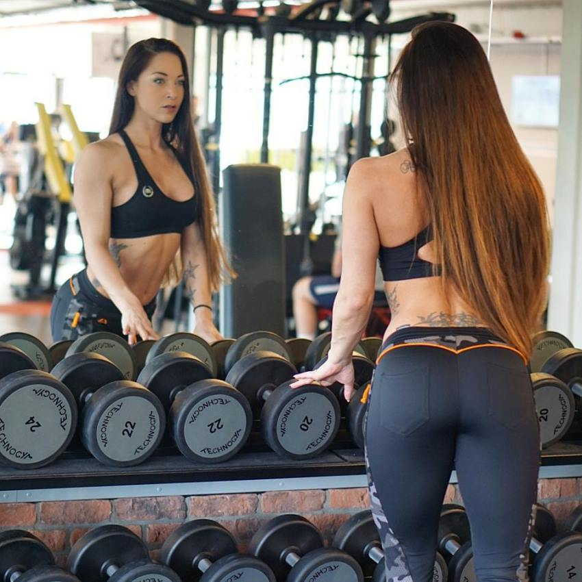 Anna Delyla leaning against a dumbbell rack and looking at herself in the mirror