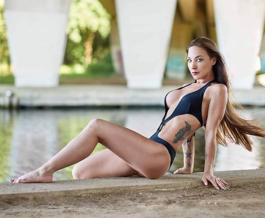 Anna Delyla sitting by a river posing for a photo