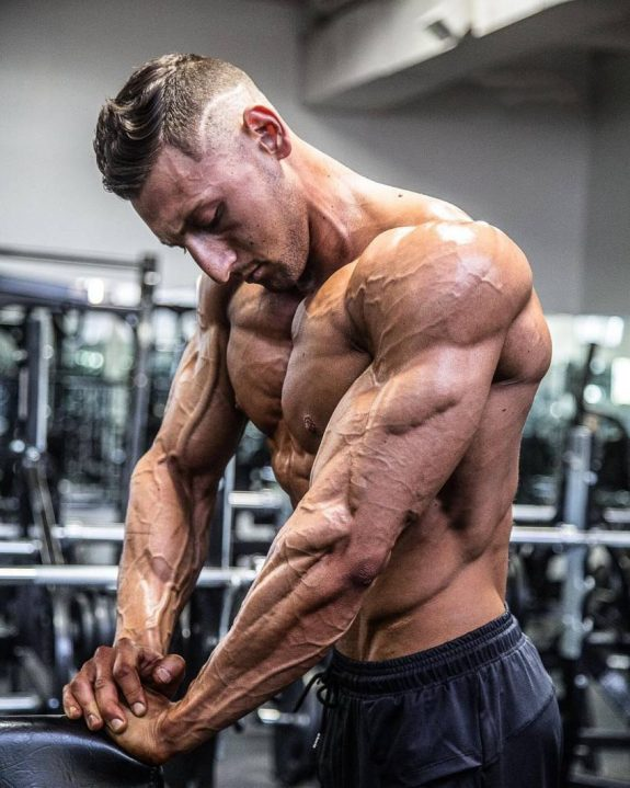 Anthony Scalza shirtless in the gym, flexing his massive and ripped triceps
