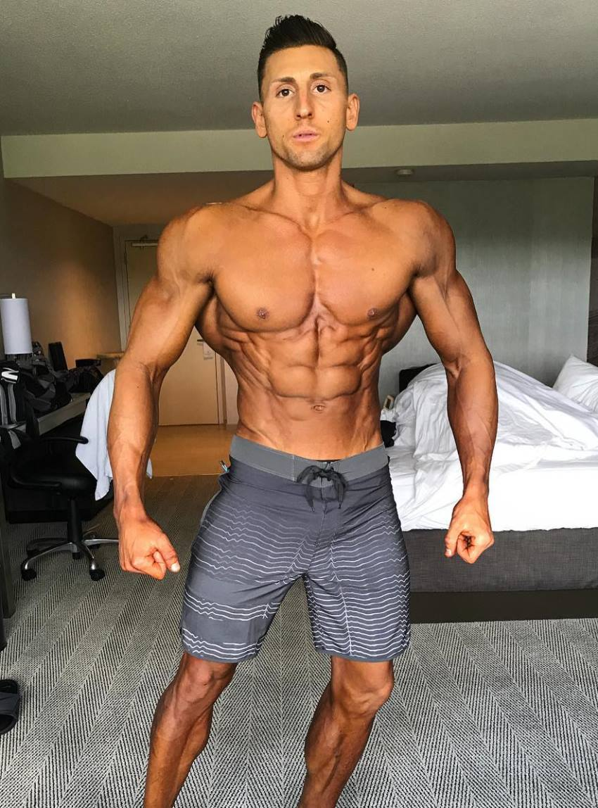 Anthony Scalza posing in his bedroom, practicing his routine for a physique show