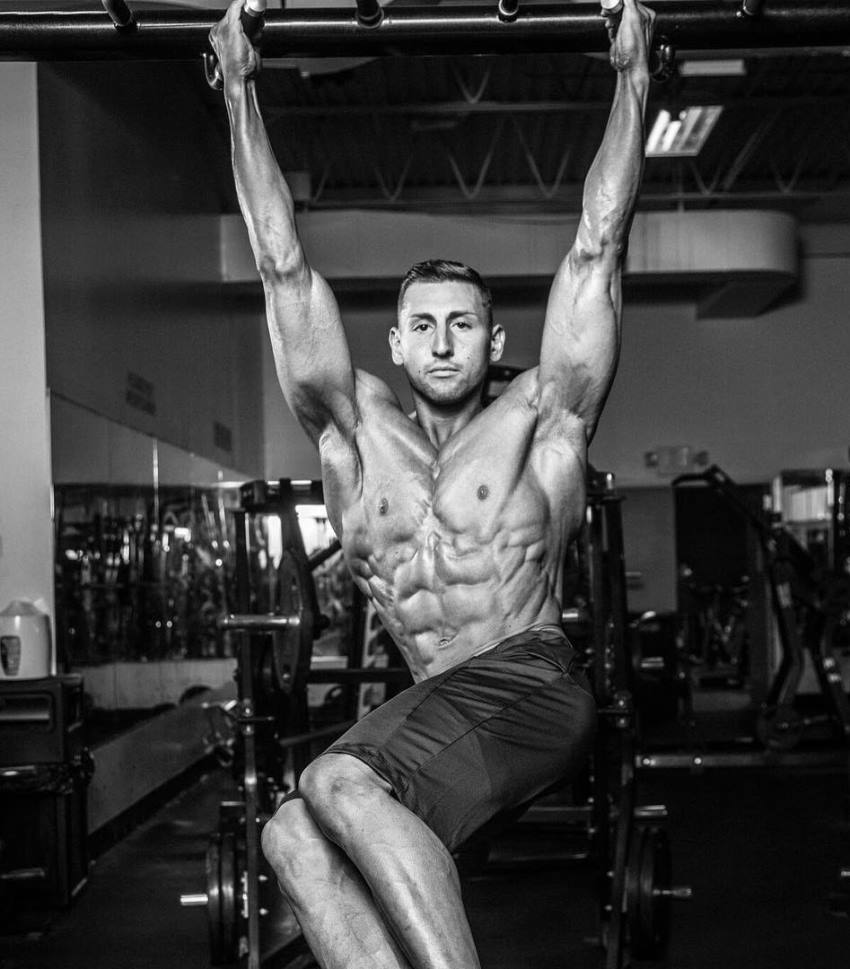 Anthony Scalza doing shirtless hanging leg raises, looking ripped and aesthetic