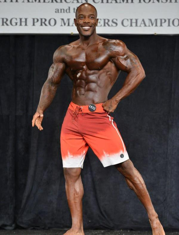 Antoine Williams smiling at the judges and showing off his muscular physique on the men's physique stage