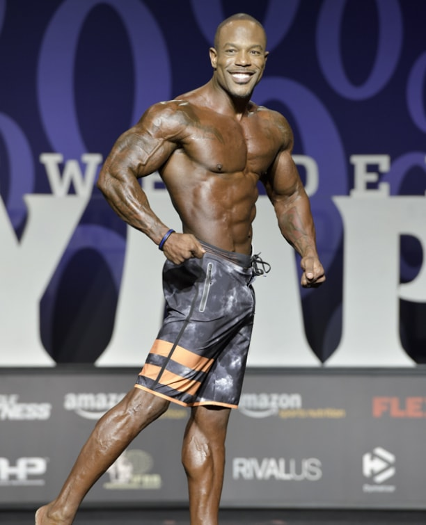 Antoine Williams smiling at the Men's Physique Olympia stage, looking ripped and muscular